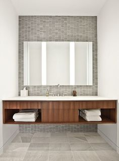 warm wood floating vanity with beautify gray tile backsplash that's really an accent wall from floor to ceiling