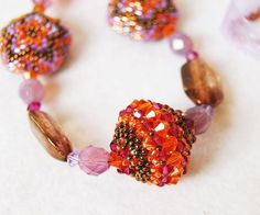 another beaded bead schema - Love the colors on this.  the orange and fuscha with metallic 11s works nicely especially with the other beads ~ Seed Bead Tutorials