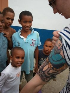 """""""I went to the Dominican Republic a few weeks ago to volunteer for an organization called Compassion International and this was one of the coolest moments of my entire trip. This community of young kids had never seen a tattoo in their life. It was amazing. It was just funny how a silly thing like a half-sleeve could break a language barrier.""""  Tattoos by Kevin Jarvis (www.kevinjarvisartwork.com)"""