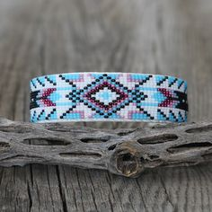 """Exquisite colors and patterns. Navajo artist, Joyce Devore hand beaded this gorgeous bracelet. The bracelet is backed with a soft leather. The entire inner circumference is about 7"""", including 1"""" opening. 7/8"""" wide When trade..."""