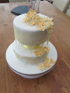 two tier yellow and cream celebration cake decorated with yellow fantasy flowers, butterflies, edible cream sugar lace and and sugar lace butterflies