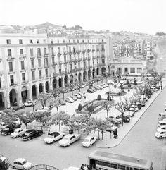 1975 girona Vista de la plaça Sant Agustí amb cotxes aparcats. En segon terme a la dreta l'edifici de la TEISA, enderrocat el 1984. Al fons la torre Alfons XII i el Barri de les Pedreres