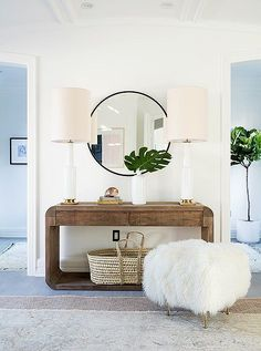 Contemporary-glam console vignette with a round mirror and sheepskin ottoman.