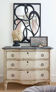 Above a chest of drawers with a distressed finish is a mirror with an artistic edge. Its inset of swirls lends contrast to the bright space.