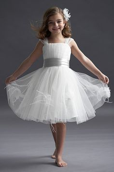 Ivory tulle tea length dress with wisteria duchess satin cumberbund sash. Tulle and feather flowers on skirt.