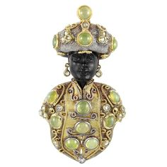 Gold, Silver, Cat's Eye, Mooonstone & Diamond Blackamoor Clip -  The carved blackamoor wearing a textured silver turban accented by gold rope-twist wire, topped by one oval cabochon grayish-green moonstone approximately 16.0 x 12.8 mm., accented by 4 round & oval cat's eyes & 9 rose-cut diamonds, his ears accented by dangling diamond earrings, adorned with a gold tunic with gold rope-twist accents...11 rose-cut diamonds, approximately 33.7 dwt.