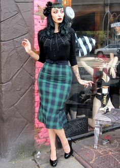 Goth pin up with a green skirt and cobweb cardigan. High heals and fascinator.
