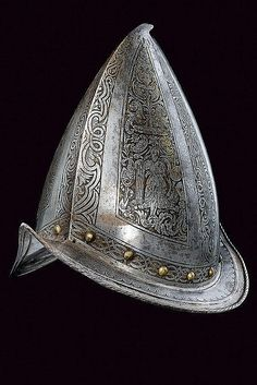 An engraved morion  dating: 19th Century  provenance: Europe  Two-halves skull ribbed at the centre, with pointed top bent toward the back; sloping, boat-shaped brim, ribbed at the edges, recessed at the margins and roped at the border. The surface of the skull decorated with engraved band featuring woven spirals and frames, grotesques, mythical animals and trophies; at the base a row of brass rivets.