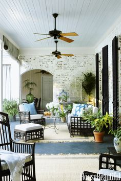 On the covered porch, the family's heirloom wicker is topped with pillows in Peter Dunham Textiles fabrics. The jute rugs are from Cost Plus World Market.