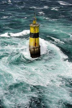 Um farol amarelo contra as ondas do mar …