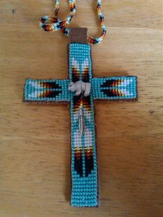 Beaded Native American style cross necklace with white buffalo bead and silver feather charm.