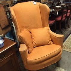 Vintage upholsered wing back chair with matching accent pillows