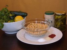 HUMMUS  Step 1: Combine the following in a food processor or blender:  2 cans garbanzo beans (chickpeas), drained  ½ cup tahini  ½ cup extra virgin olive oil  juice of two lemons  ½ bunch cilantro  ½ cucumber, peeled and cubed  a dash of pickle juice  1 tsp. garlic powder  ½ tsp. each salt and paprika