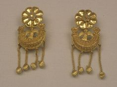 Earrings of the 5th century BC. Gold filigree-decorated earrings from Eretria, Euboea (Greece). They have green enamelled rosettes and eight tiny pendants in the form of cockle-shells. On top of the crescent sits a siren.
