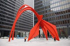 """Alexander Calder's """"Flamingo,"""" Federal Center Plaza. Surrounded by three glass-box office towers designed by Mies van der Rohe, the sculpture's bold vermilion color and 53-foot-tall arches complement the black, rectilinear-shaped skyscrapers."""