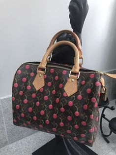 eac5dcc7580d The Louis Vuitton Cherry Blossom Monogram Canvas Papillon Bag has leather  handles and inserts with golden studs