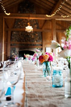 mason jars and apothecary vases used with simple flowers in lieu of formal center pieces