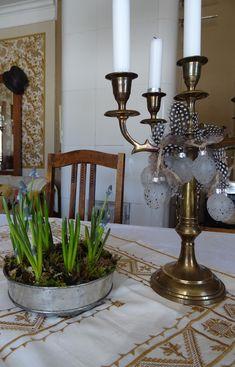Helmililjat ja vanha kynttelikkö pöydällä.