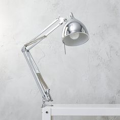 clamp lamp. Genes are retro luxo, vibe is slick CB2 chrome. Industrial steel task light in gleaming chrome powdercoat vise-clamps workshop style to any flat edge—desk, bookcase, nightstand, side table—to angle the beam where you need it. Teardrop shade swivels side to side; two hinges raise/lower light. On/off line switch; clear cord.