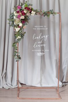 Elegant yet modern, this acrylic sign will be a showstopper at your wedding or event. The copper arch can be accented with lush florals like this one in pinks, burgundy and eucalyptus. Flowers by Gypsy Annie.    Photo by Alisha Faith Photography.    Arch by Brittany Anne's Rentals    #weddingsign #weddingdaydecor #weddingreception #acrylicsign