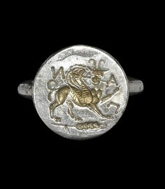 GREEK SILVER-GILT INCUSE CHIMAERA RING 3rd-1st century BC.  A silver-gilt finger ring comprising a round-section hoop; the bezel a disc with intaglio design of a chimaera or lion-griffon with raised foreleg and looped tail, standing on an ear of corn, based on a coin of Panticapaeum; the legend ΠAN (Pan) surrounding.
