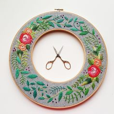 These beautiful wreaths are hand embroidered using cotton floss on fabric, framed in a double wooden embroidery hoop. The pattern features roses and greenery,