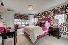 Fabulous girl's room with Dedar Alhambra Wallpapered accent wall framing windows dressed in gray and pink floral roman shades on either side of the hot pink velvet bed dressed with pink and white bedding topped with gray and pink floral pillows.