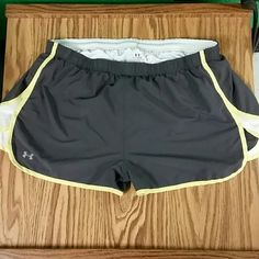 UA heatgear shorts size XL UA heatgear shorts size XL in EUC!  Color is grey with yellow trim. Shorts have a drawstring in front for tightening, built in panty liner, and a hidden $ pouch in front right of the lining. Under Armour Shorts