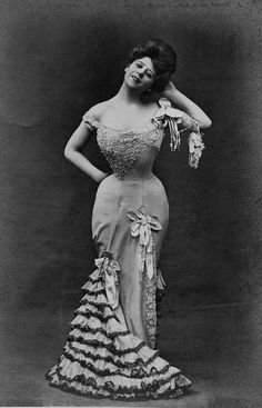Camille Clifford. In this picture, you can see how tiny her waist was. I like how the dress is asymmetrical. The lace on the top and the sleeve shows a very delicate touch of the designer. The flowers and the ruffles soften the dress