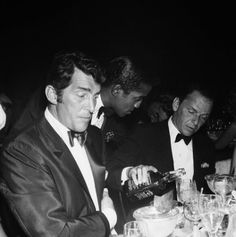 Singer Dean Martin and Sammy Davis, Jr. sit at a table as fellow singer and Rat Pack member Frank Sinatra pours Jack Daniels from a bottle at the Cocoanut Grove during Eddie Fisher's opening night on July 1961 in Los Angeles, California. Dean Martin, James Dean, The Rat Pack, Joey Bishop, Sammy Davis Jr, Humphrey Bogart, Jack Daniels, Classic Hollywood, Old Hollywood