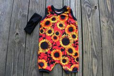 This sunflower romper features a fire red background with an assortment of black and golden orange sunflowers. Show your baby girl fierce personality as you make the perfect outfit by matching this ro