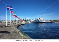 Helsingborg, Sweden - 04 May, 2018: Europe country flags flap in the wind at harbour and Scandlines ferry boat cruising from Helsingborg Sweden to Helsingor Denmark