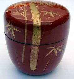 red lacquered wood tea caddy (natsume) with gold maki-e bamboo design; ō-natsume (large jujube fruit) shape; unmarked.