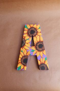LOVE SUNFLOWER THINGS. I LOVE SUNFLOWER PATTERNS I WOULD TOTALLY LOVE A SHIRT WOTH LETTERS ON IT WITH SUNFLOWERS ON IT. I didn't see that pattern at collegiate but I love sunflowers just throwing that out there Sunflower Room, Sunflower Shirt, Sunflower Canvas, Sunflower Crafts, Sunflower Pattern, Paper Mache Letters, Painting Wooden Letters, Painted Letters, Alpha Omicron Pi