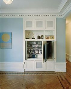A compartment in this built-in shelving unit allows the TV to be tucked out