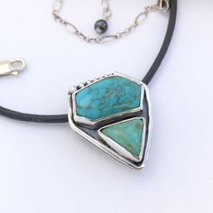 Turquoise pendant featuring a free form hexagonal Kingman Turquoise stone and a triangle shaped Elisa Mine turquoise stone. The stones are set in fine and Sterling silver and arranged in a contemporary design with seven solid Sterling balls along ...