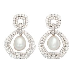 DAVID WEBB Pearl and Diamond Drop Earclips.The impressive baroque pearls are suspended within a double row of the whitest and brightest round diamonds. USA 1960s