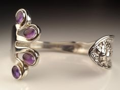 Dinner fork Cuff with Amethyst by SilverWears on Etsy. $78.00 USD     I like the twist on the usual flatware jewelry by the addition of the amethyst in the tines.