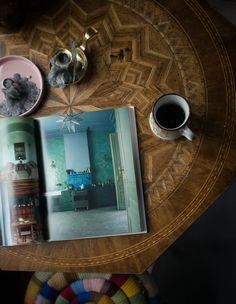 Inspiration sombre et mystérieuse épinglée par Tiffany Fayolle, architecte d'intérieur et décorateur à Lyon. magazine ouvert page décoration verte et bleue table ronde en marqueterie et pouf multicolor