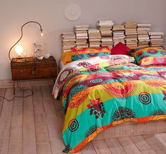 Quirky bohemian bedroom. Bright boho quilt, stacked books as a bed head and vintage side table.