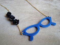 Colar em corrente de metal dourada com rosinhas de resina na cor preta e óculos gatinho em resina azul. R$29,90