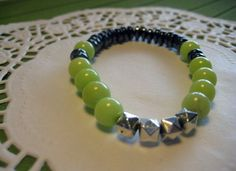 Title: Lime and stone bracelet  Add a pop of color with this beaded bracelet that'll complement your unique spirit! $30.CAD  Four geometric metal beads along the contrasting colour of the green mountain jades and the black, roundel hematite is the best choice of spring jewelry.