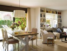 Salón comedor con librería alrededor de la ventana y vistas al jardín