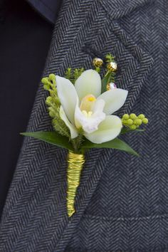 Cymbidium boutonniere with elegant greens and gold detailing.