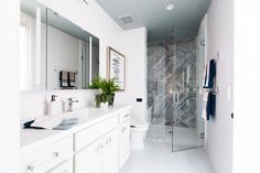 The attractive terrace bathroom with a light blue and navy color scheme includes a white painted vanity with clear Lucite hardware and a walk-in shower with a show-stopping tile design.