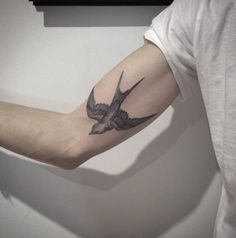 Swallow tattoo on the right inner arm.