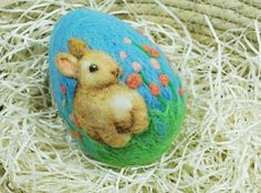 Easter Bunny on Needle Felted Egg This cute little bunny is just the guy to bring a smile as he sits in his flower garden on this solid wool egg. Use this egg in your Easter table display or in any holidy decor. It would make a lovely gift as well. The egg is about 3 1/4 high and 2 1/4