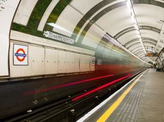 Long exposure photo of Gloucester Road tube station with a tube train passing through.