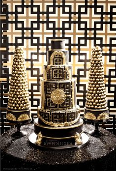 Black and gold wedding cake with geometric backdrop.