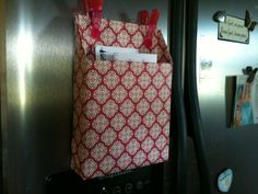 Cereal box covered in scrapbook paper with magnets on the side of the fridge.  Great place to put the mail pile or menus.  Must do!!!